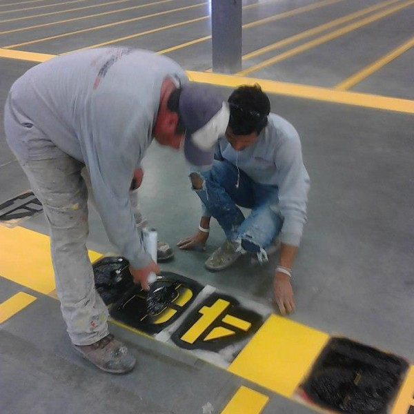 Employees of Stripe-a-Zone painting lane numbers inside warehouse.