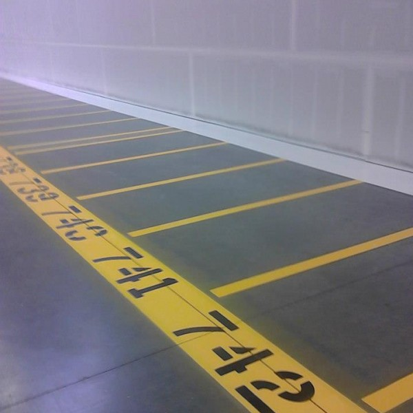 Picture showcasing numbered stripes and lanes inside a warehouse.